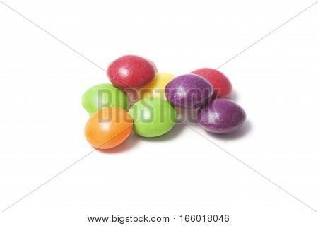 Few colorful small rounded candies on white background