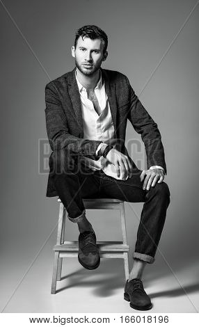 Studio fashion shot: portrait of a handsome young man in jeans shirt and jacket sitting on bench. Black and white