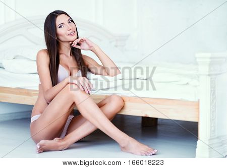 Attractive sexy young woman in underclothes sitting at a bed
