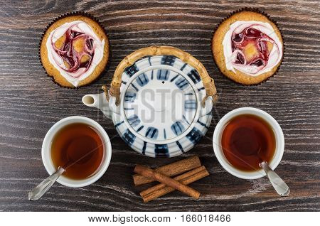 Cakes, Cups Of Tea, Cinnamon Sticks And Teapot On Table