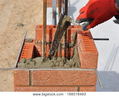 Bricklaying closeup. Bricklayer hand holding a putty knife and building a brick fence column with iron bar.