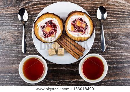 Two Cakes, Lumpy Sugar, Cinnamon Sticks In Plate And Tea