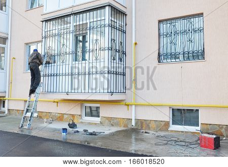 Contractor installing window iron security bars. Security bars for windows and balcony