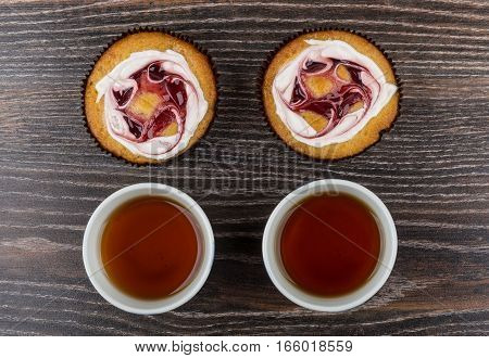 Two Cakes And Cups Of Hot Tea On Dark Table