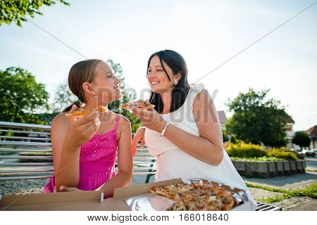 Daughter and mother holding pizza slice. Enjoying leisure time outdoors.