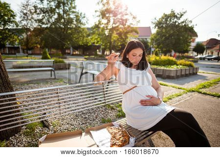 Pregnant woman eating unhealthy pizza. Sitting on park bench.