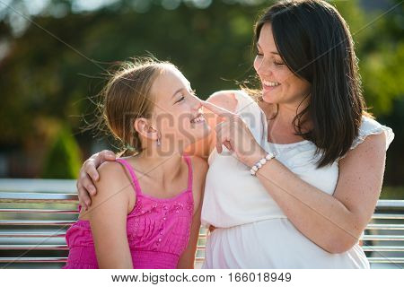 Cute little daughter having fun with her mother outdoors.