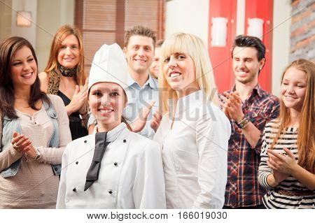 a chef and a waiter are posing in front of their happy guests