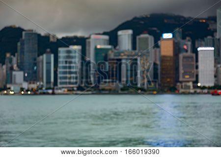Blurred bokeh lights Hong Kong office building over coastline after sunset