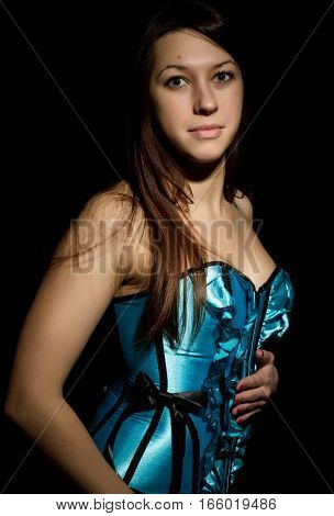 portrait of a sexy young woman in corset with lacing posing on a dark background.