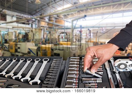 Hand of a man who handled tools with blurred of factory for background.