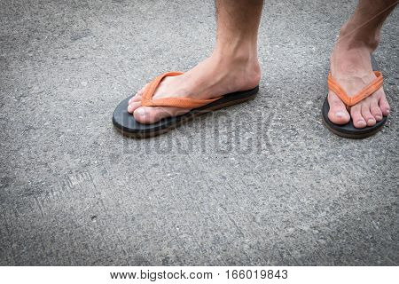 Feet of a man wearing sandals on the old concrete floor.