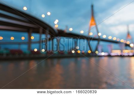 Blurred bokeh lights suspension bridged over city river abstract background