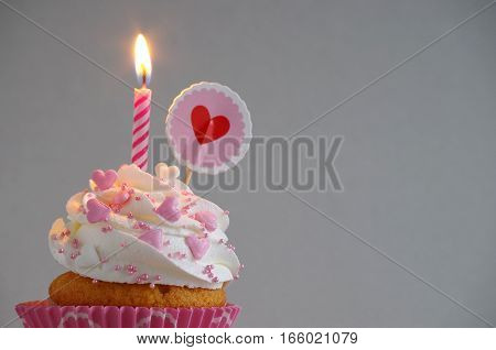 homemade birthday cake with whipping cream, sugar sprinkles and heart