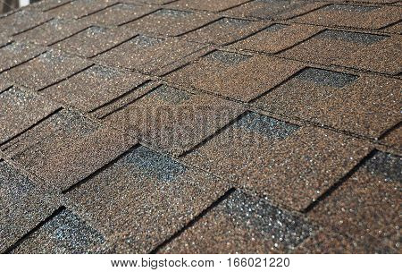 Close up on brown asphalt shingles roof. Roofing Construction Exterior.