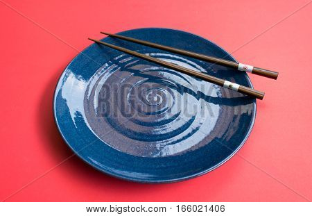 Blue plate with chopsticks Japanese style pink background.