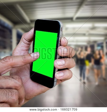 Man hand holding and using mobilecell phonesmart phone with isolated screen with blur image of people for background.