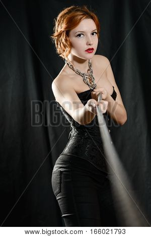 Attractive red-haired girl in black corset pulls the chain hands chained to the neck
