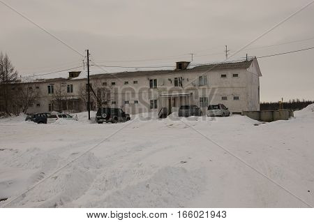 Old two-storied  house in winter with snow, cars and trees on the yard. Poverty and misery, North