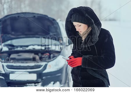 girl on the winter road is calling the phone near the car