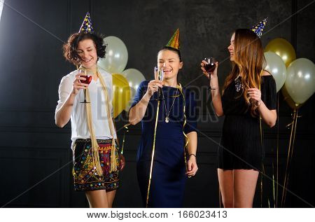 Three young women celebrate someone's birthday. In hands at everyone a glass with champagne. They are elegantly dressed. Cheerful birthday party.