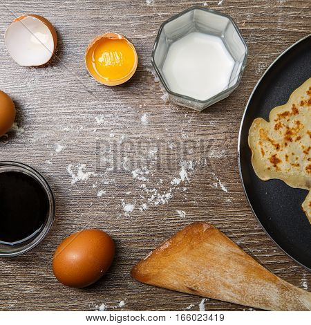 Wooden table with frying pan with pancake, eggs, milk