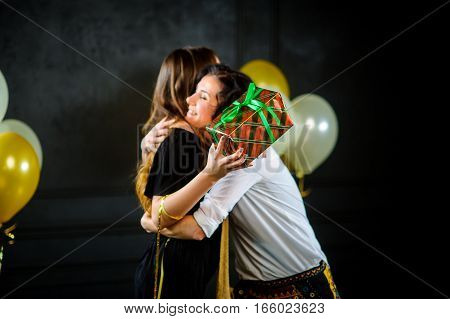 The young woman congratulates the girlfriend and gives her a box with a gift. Women joyfully embrace. The room is decorated with balloons.