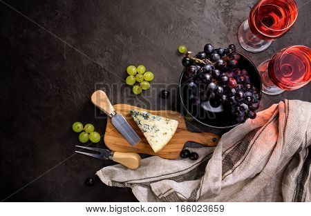 Blue cheese, parmesan, wine and grapes on dark stone background. Food background with copyspace. Top view