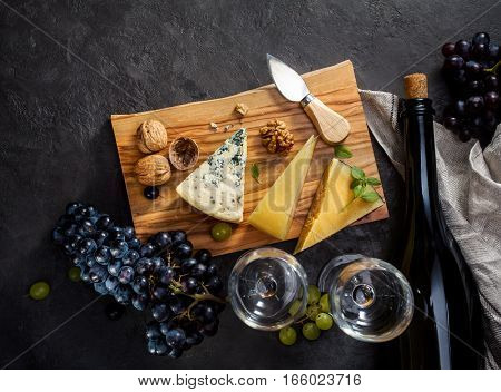 Blue cheese, parmesan, wine and grapes on dark stone background.