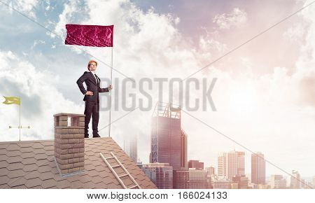 Businessman standing on house roof and red holding flag. Mixed media