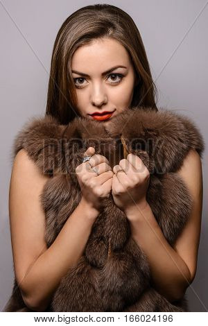 The girl in a fur coat on a light background. Beauty Fashion Model Girl in Black Mink Fur Coat. Beautiful Luxury Winter Woman. Fashion Model Girl Portrait with jewelry wearing