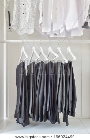 Row Of White Shirts And Black Pants Hanging In Wooden Wardrobe