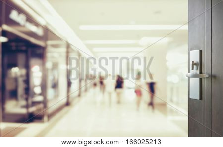 Opened Wooden Door To Blurred People Shopping In Department Stor