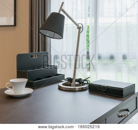 Wooden Table With White Coffee Cup And Reading Lamp In Modern Working Room Interior