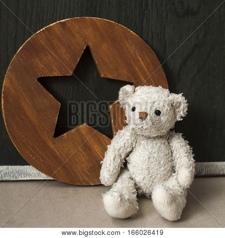 White teddy bear. favorite toy on the background of the old wooden star