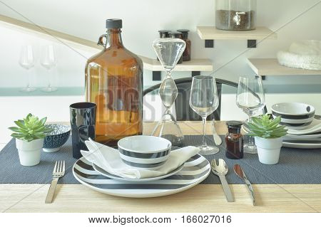 Striped Chinaware, Wine Glass And Bottle Setting On Wooden Dining Table
