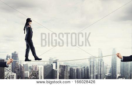 Businessman with blindfolder on eyes walking on rope over cityscape background