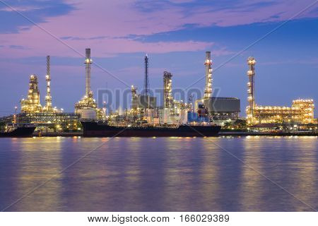 Oil refinery factory river front with beautiful twilight sky background