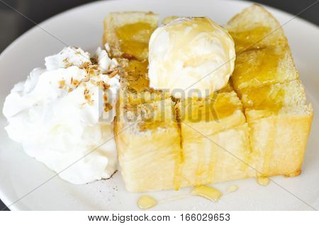 Honey toast with vanilla ice cream whipped cream and syrup dish