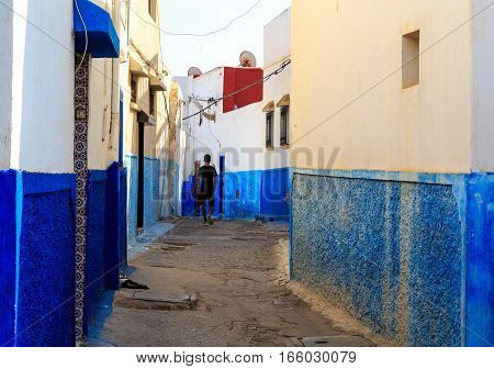 Man Walking In The Small Streets In Blue And White In The Kasbah Of The Old City Rabat In Marocco