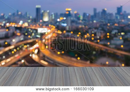 Opening wooden floor blurred bokeh lights highway intersection with city downtown background