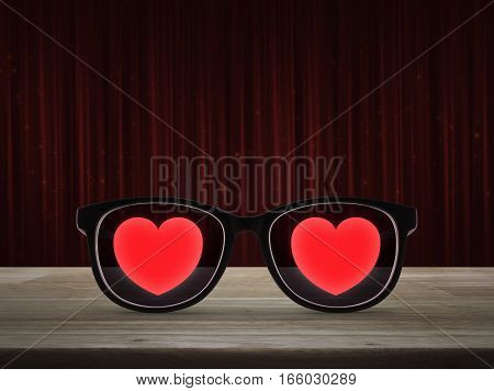 Love heart with eye glasses on wooden table over red curtain with sparkle glitter Valentines day concept