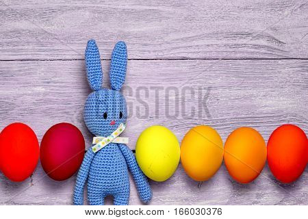 Amigurumi Toy Easter Bunny With Colorful Eggs In A Row On A Wooden Table - Easter Background With Co