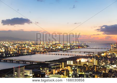 Blurred bokeh light aerial view Osaka city skyline night view. abstract background