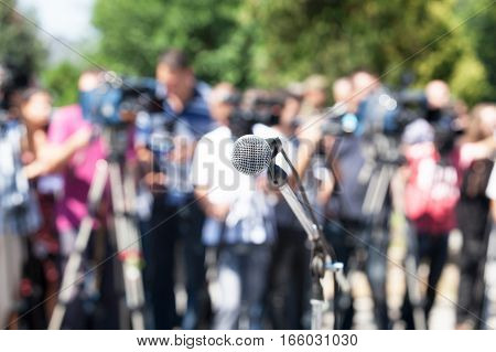 News conference. Microphone in focus, blurred camera operators and reporters in background.