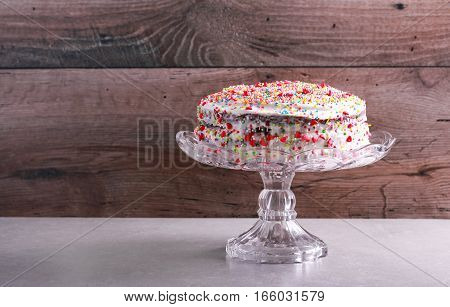 Layered cake with cream frosting sprinkled with hundreds and thousands