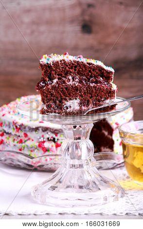 Chocolate layered cake with cream and cherry