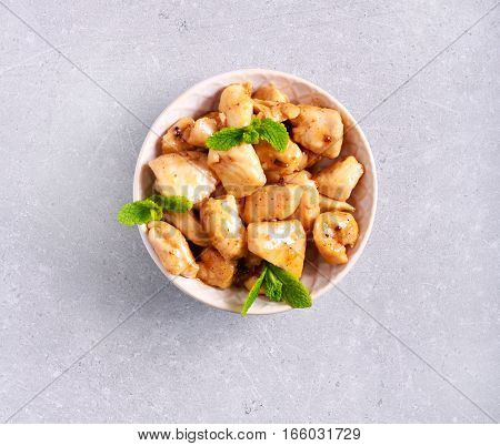 Lemon and mint chicken breast in a bowl top view