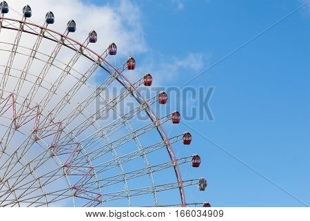 Big Ferris wheel in amusement Park close up with blue sky background