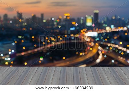 Opening wooden floor blurred bokhe city lights with sunset sky background